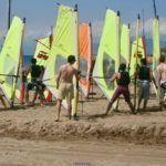 Cours de planche à voile: exercices sur la plage avec la voile.